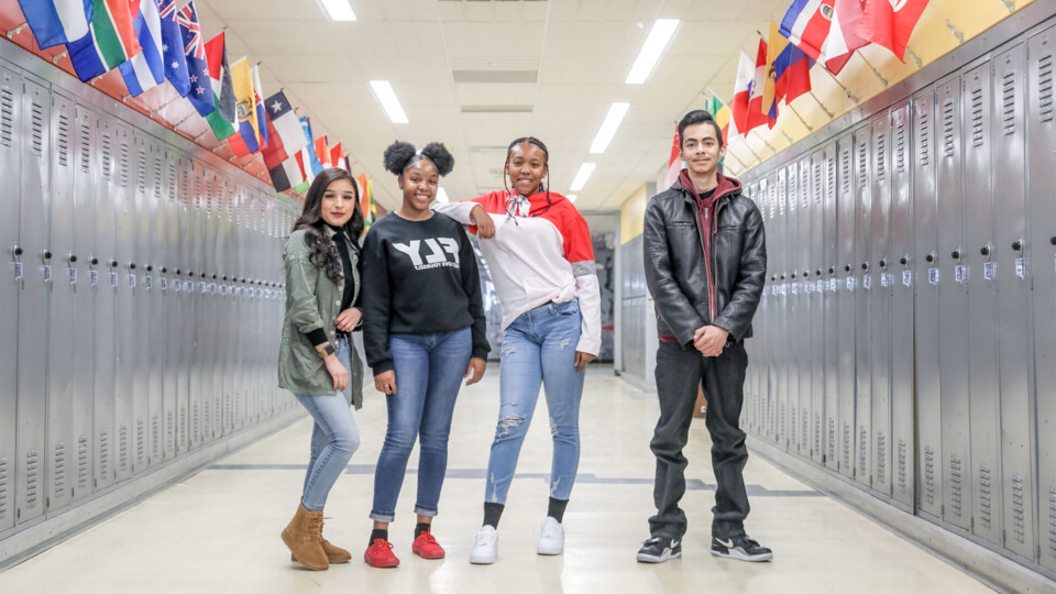 Four students standing in the hallway of a Far Northeast campus